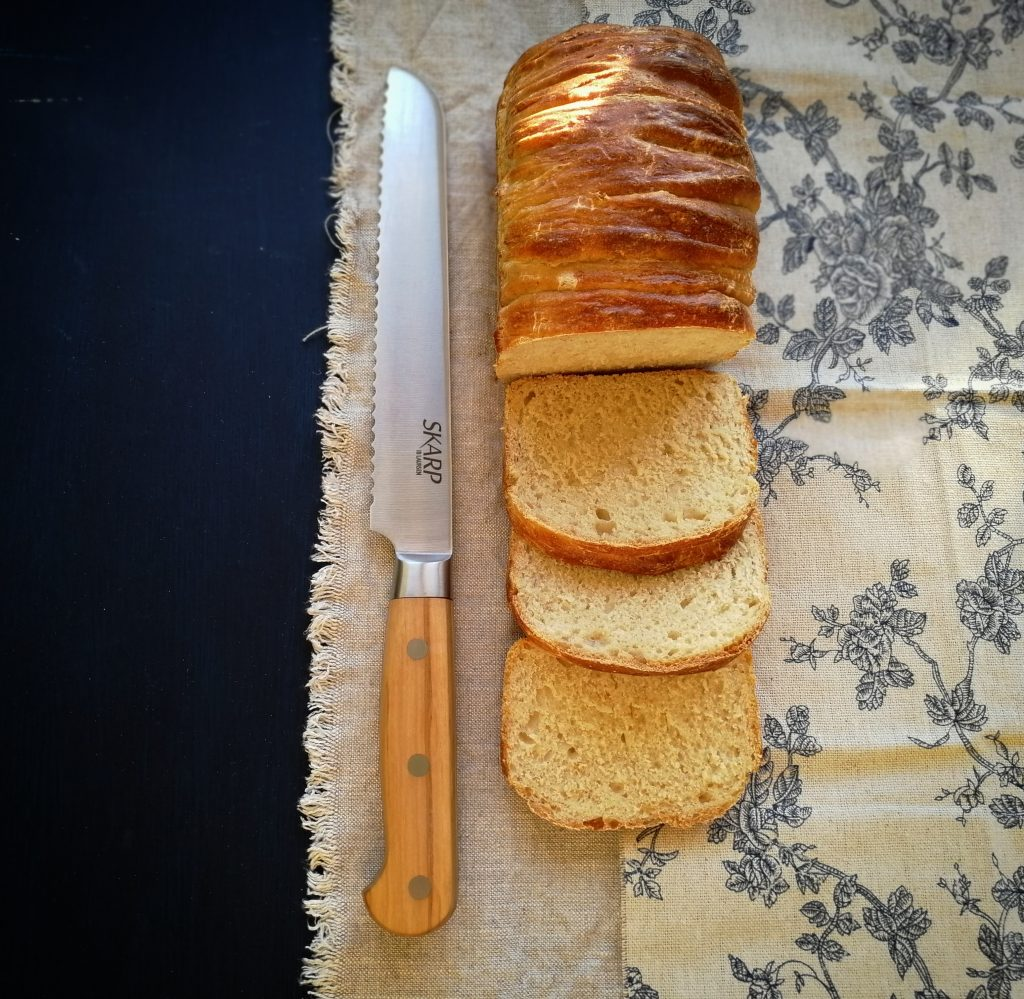 A tin loaf of golden bread with a bread knife
