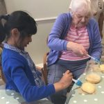 A care home resident glazing buns with a child